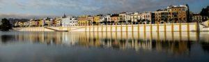 barrio de triana en sevilla desde el otro lado del rio con reflejos